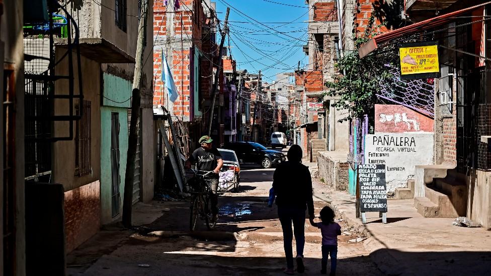 Una madre y su hijo caminan en un barrio pobre en Buenos Aires
