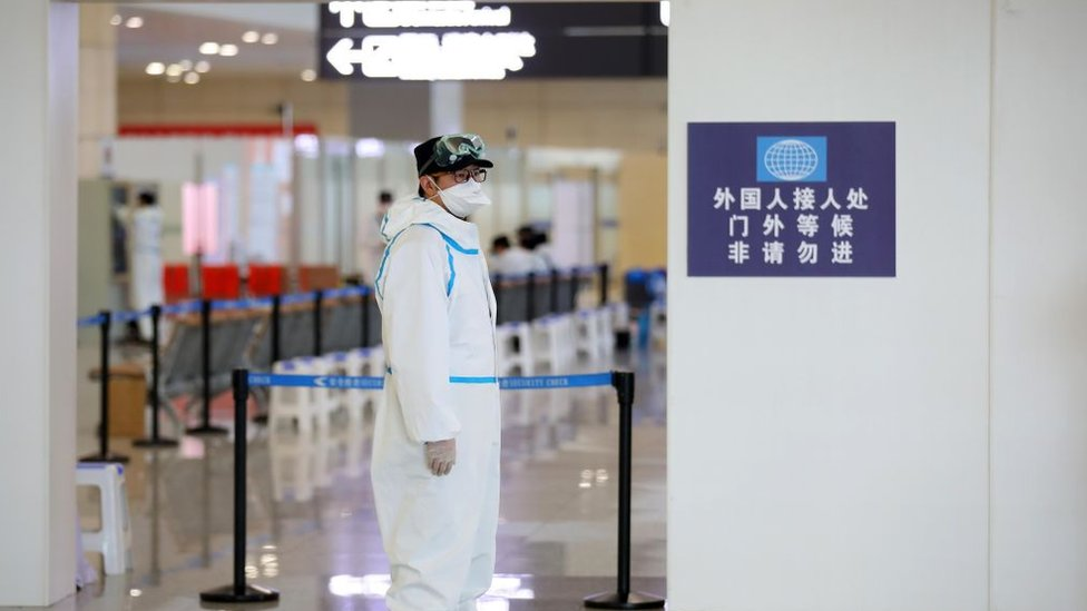 Funcionario con equipo de protección personal en el aeropuerto de Nanjing, marzo 2020