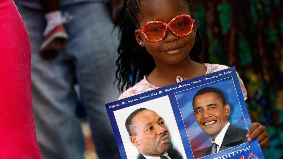 Niña con letrero con las imágenes de Martin Luther King y Barack Obama
