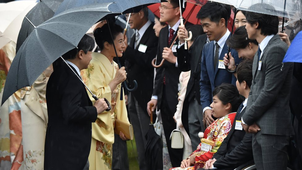 Japan's Crown Prince Naruhito and Crown Princess Masako greet guests during an autumn garden party at Akasaka Palace Imperial garden in Tokyo