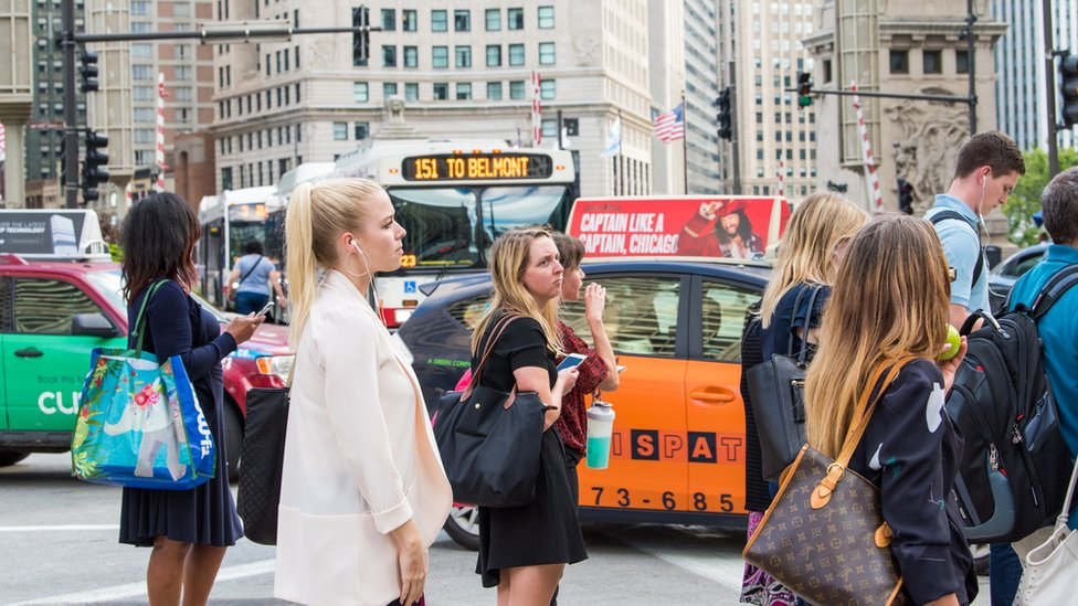 Commuters in Chicago wait for a bus