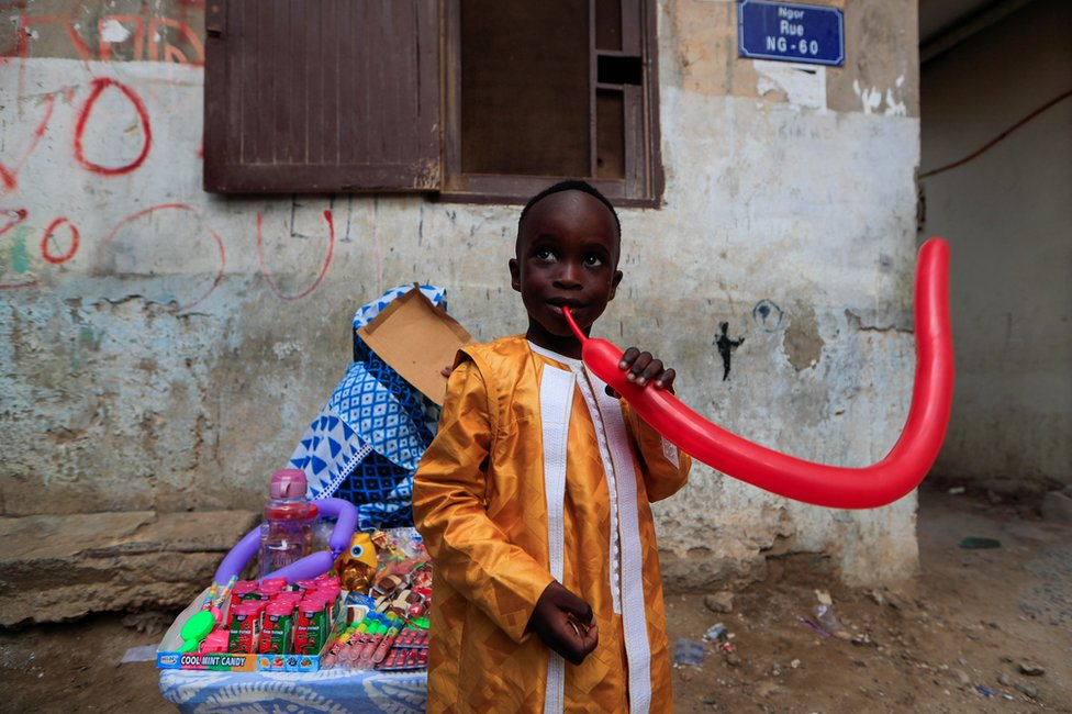 A boy tries to inflate a balloon.