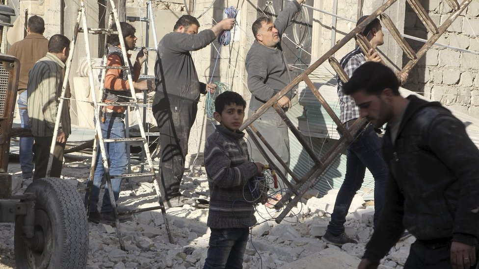 Residents inspect damage after an air strike on the rebel held al-Fardous district of Aleppo, Syria (18 February 2016)