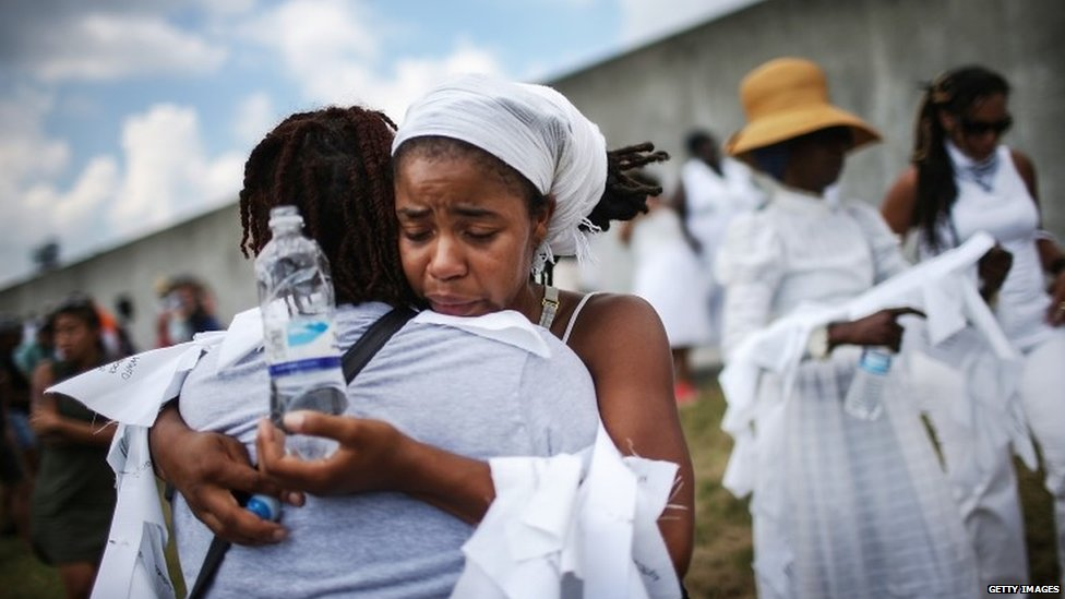 Savannah Shange hugs a woman in front of the repaired levee wall in the Lower Ninth Ward