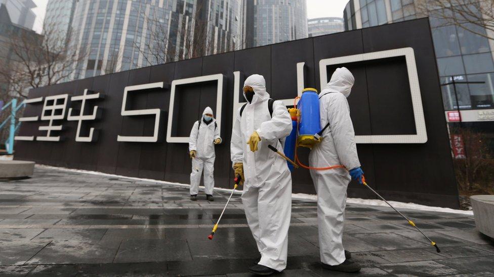 أشخاص يجرون عمليات تعقيم في بكين