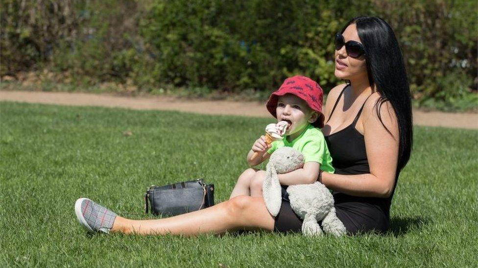 Jayden Lynch, three, eats an ice cream alongside Katie Lynch, 28