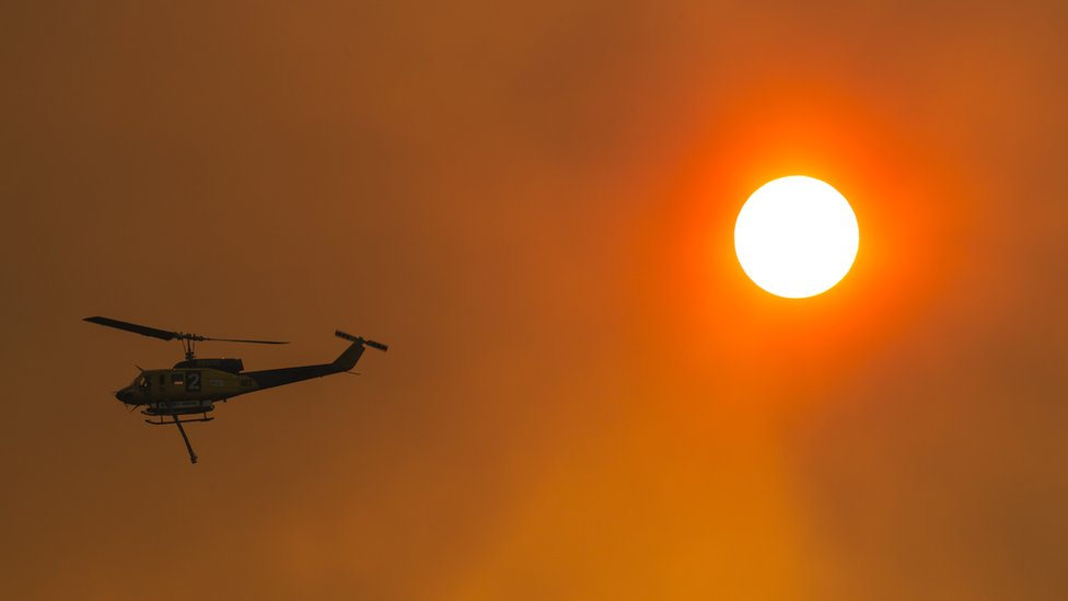 A water-bombing helicopter silhouetted on a red, smoke-filled sky next to the sun