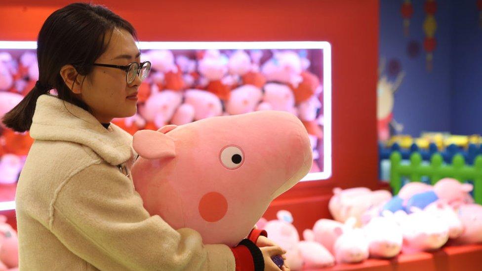 Mujer con muñeco de Peppa Pig