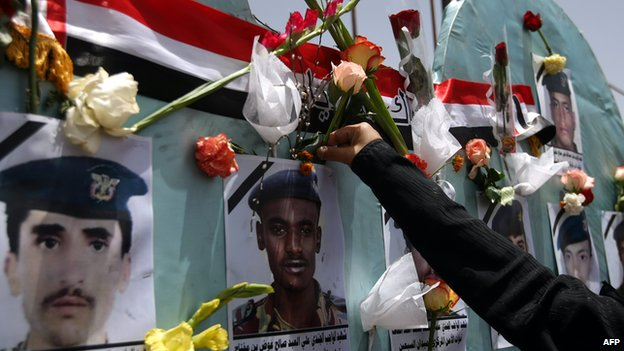 A woman places a flower on a memorial to Yemeni soldiers killed in an al-Qaeda suicide bomb attack on a parade rehearsal in Sanaa in May 2012