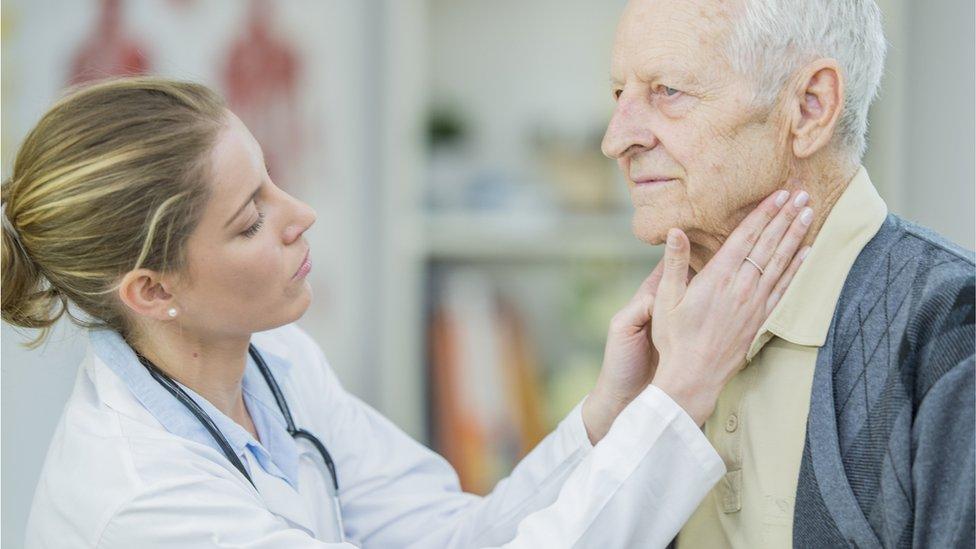 Una médica revisa los ganglios de un hombre mayor.