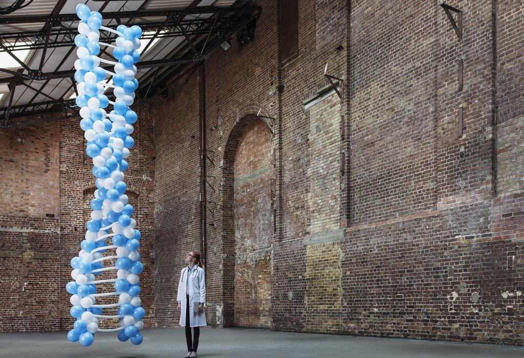 Chica mirando un helix de ADN hecho de globos