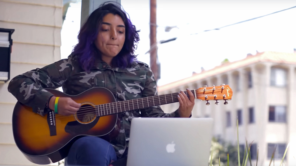 A young woman learning to play guitar