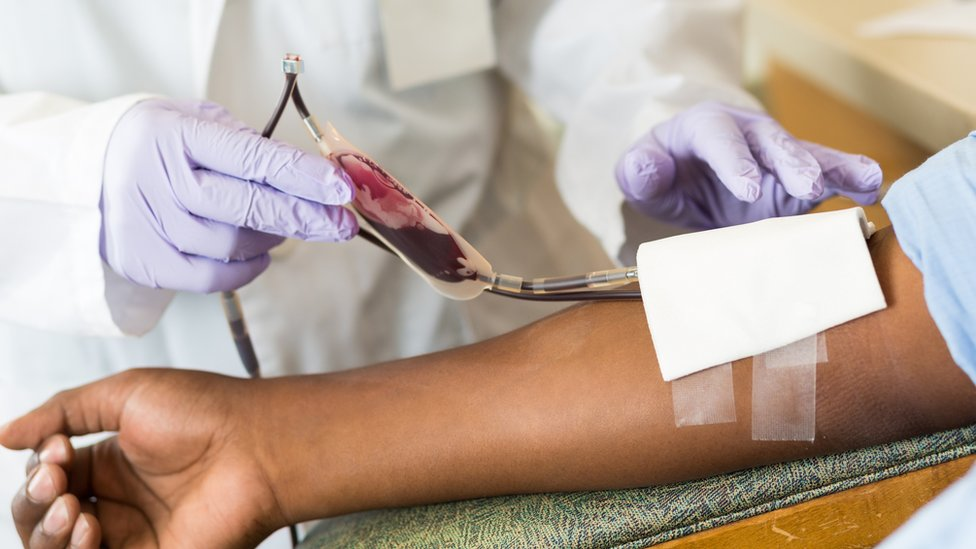Nurse checking bag of blood while patient gives donation