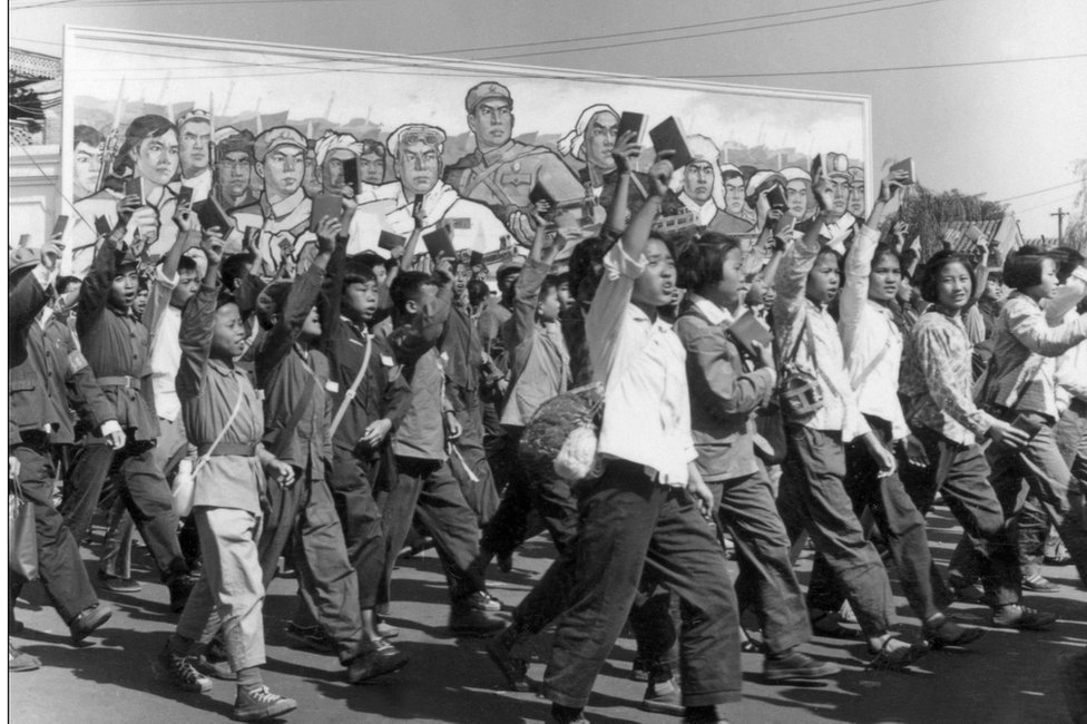 """School and university Red Guards, waving copies of Chairman Mao's """"Little Red Book"""", in a June 1966 parade in Beijing"""