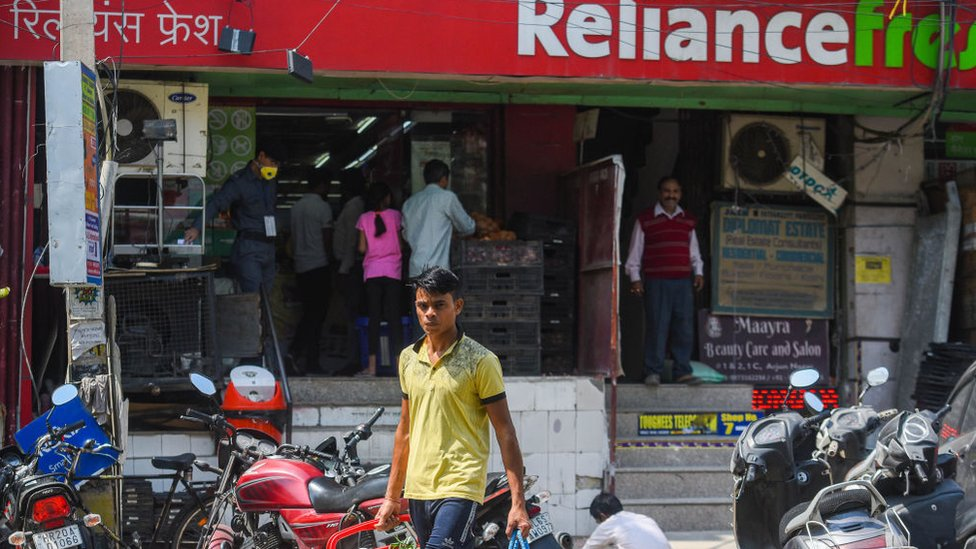 Man with shopping bags in front of Reliance grocery store.