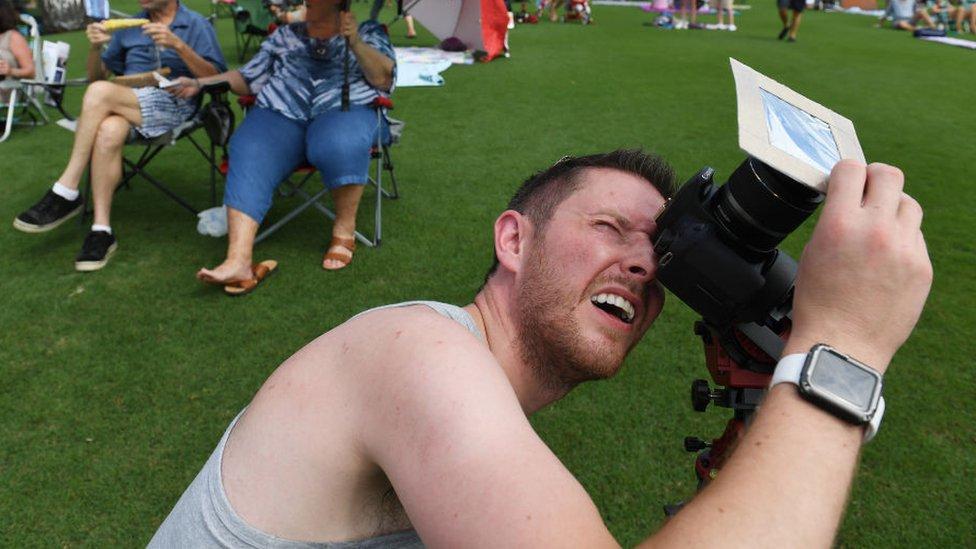 Hombre sacando foto a eclipse solar total.
