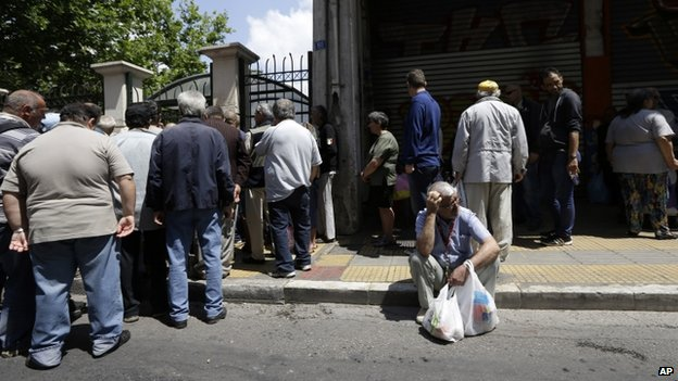 People wait for a soup kitchen to open, organised daily by the municipality in Athens