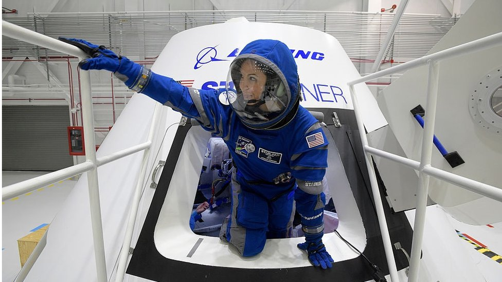 Boeing propulsion engineer Monica Hopkins climbs out of a mockup of the CST-100 Starliner crew module, while wearing a newly-designed spacesuit.