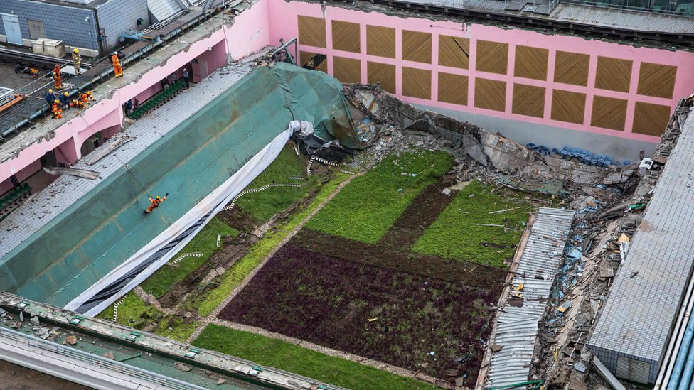 rescue workers (orange suits, L) inspect a sports centre after its roof collapsed at the City University in Hong Kong