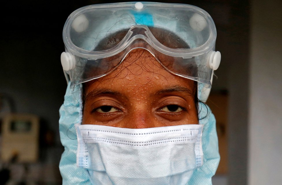 Beads of sweat run down the forehead of a healthcare worker wearing protective gear