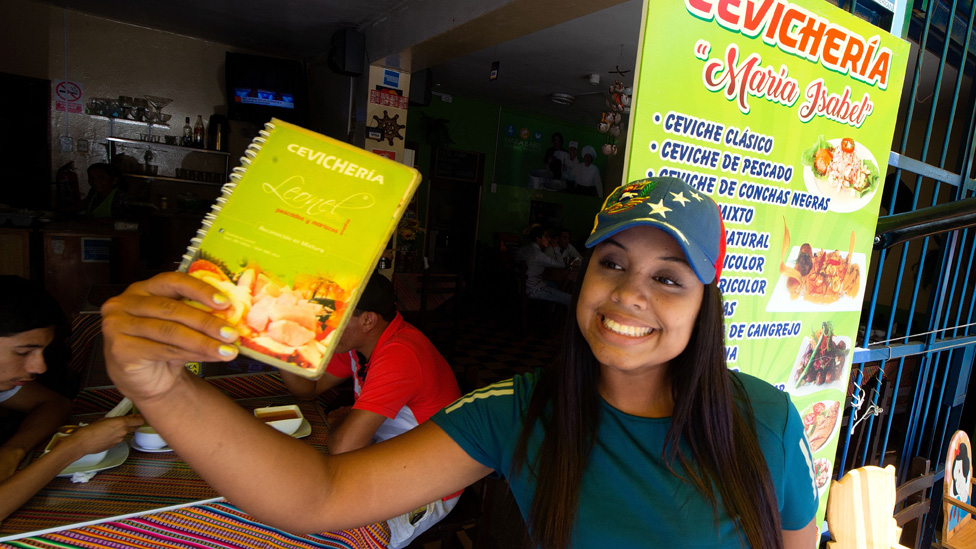 Venezuelan Liriannys Antoima calls passers-by into a restaurant where she works as a waitress in Lima on April 4, 2019.