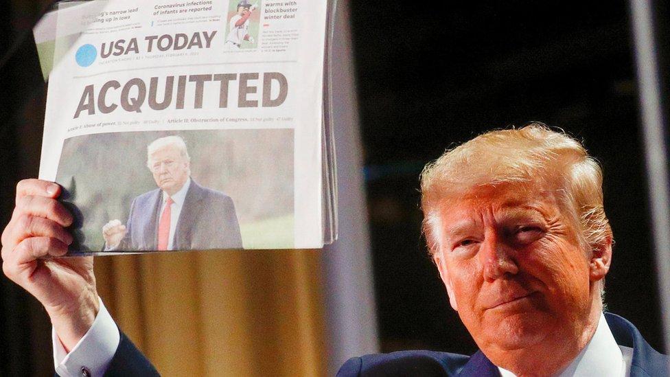 ترامب يحمل صحيفة تحمل خبر برائته في المساءلة الأولى أمام مجلس الشيوخ