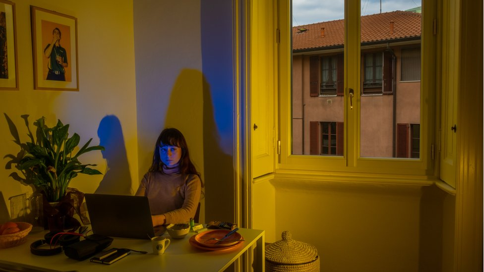 Lucia is seen sitting alone in her apartment, using a laptop at a table