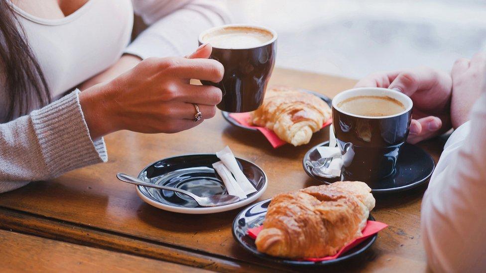 Personas tomando café con croissants.