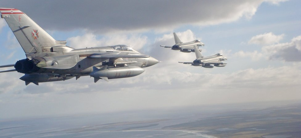 An RAF Tornado F3 Navigator escorts Typhoon jets as they fly over the Falkland Islands