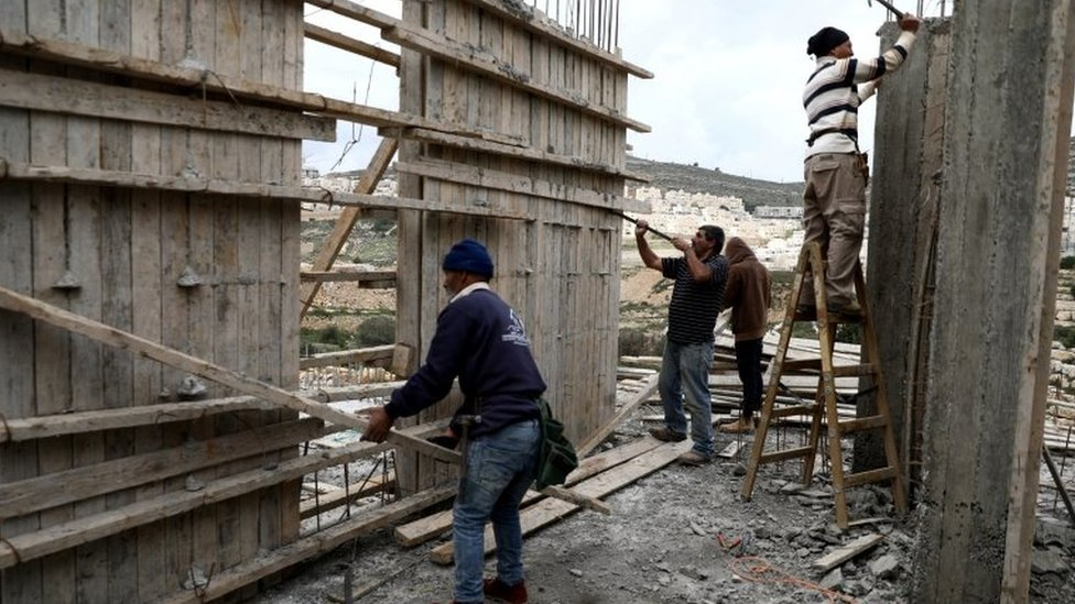 File photo showing Palestinians working at a building site at the Israeli settlement of Ramat Givat Zeev on 19 March 2020
