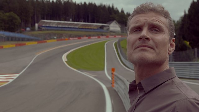 David Coulthard poses in front of Eau Rouge
