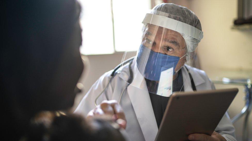 Profissional de saúde com face shield fala com mãe e filho de costas, todos sentados em consultório