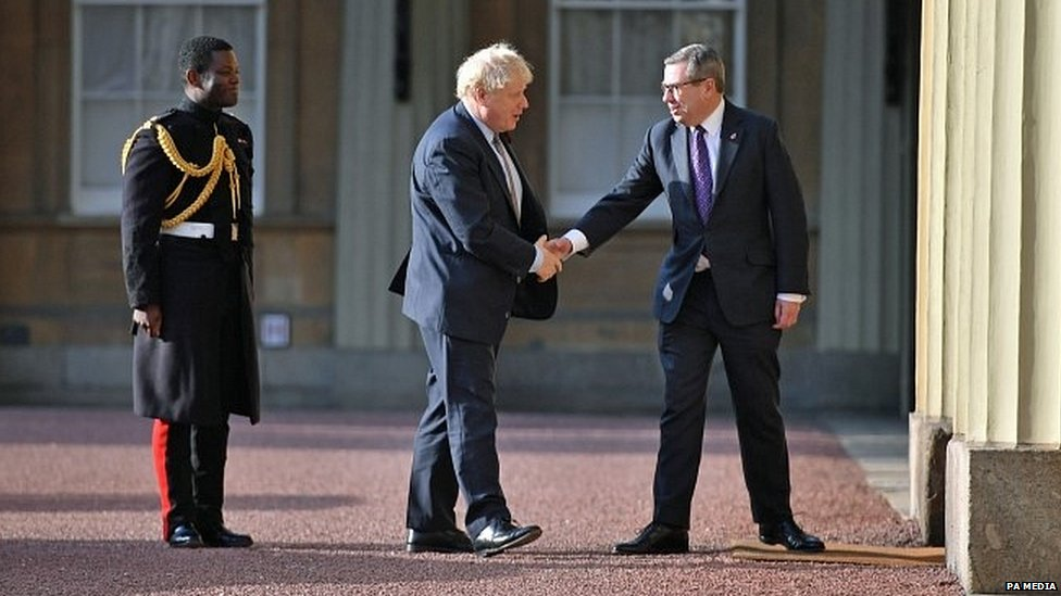 Boris Johnson greeted by royal officials as he arrives at Buckingham Palace