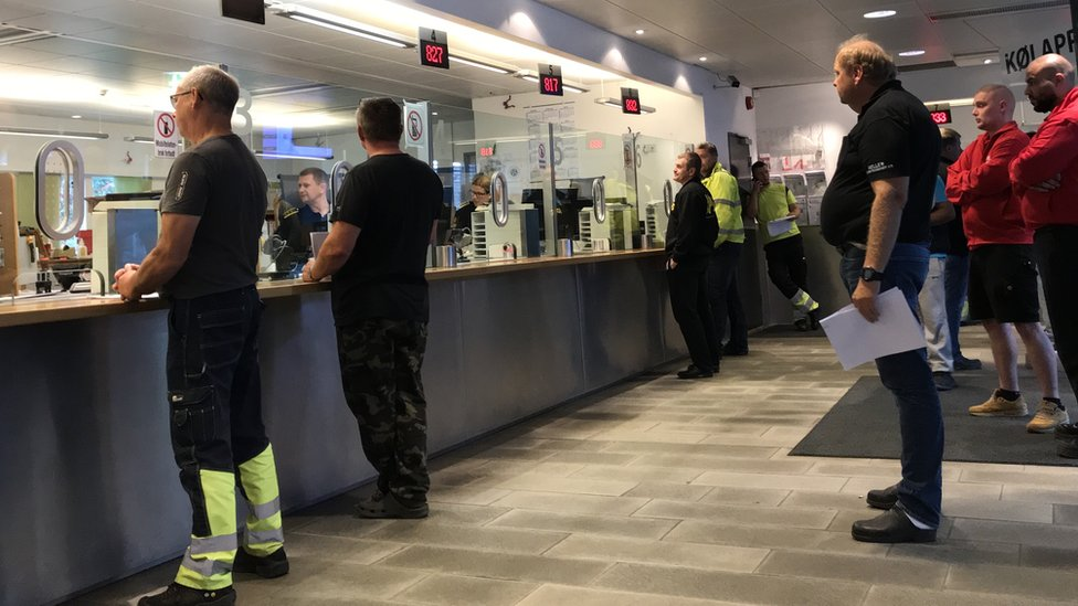 People queuing inside a Norwegian customs office