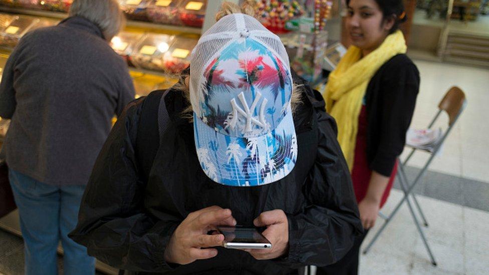 Hombre mirando de cerca su celular