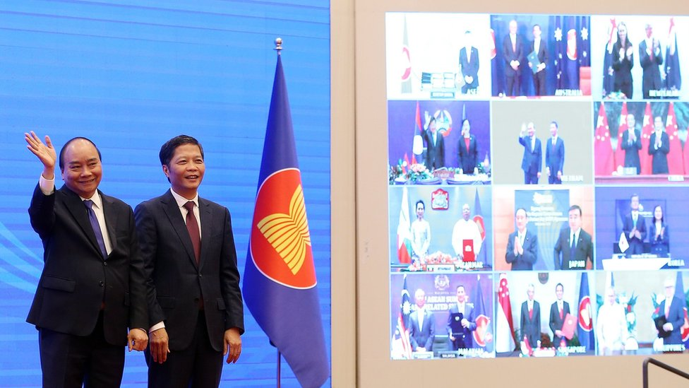 "Vietnam""s Prime Minister Nguyen Xuan Phuc (L) and Minister of Industry and Trade Tran Tuan Anh (R) cheer after the virtual signing ceremony for the Regional Comprehensive Economic Partnership (RCEP) in Hanoi, Vietnam, 15 November 2020."