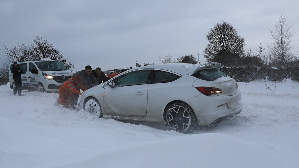 Men push a car in the snow