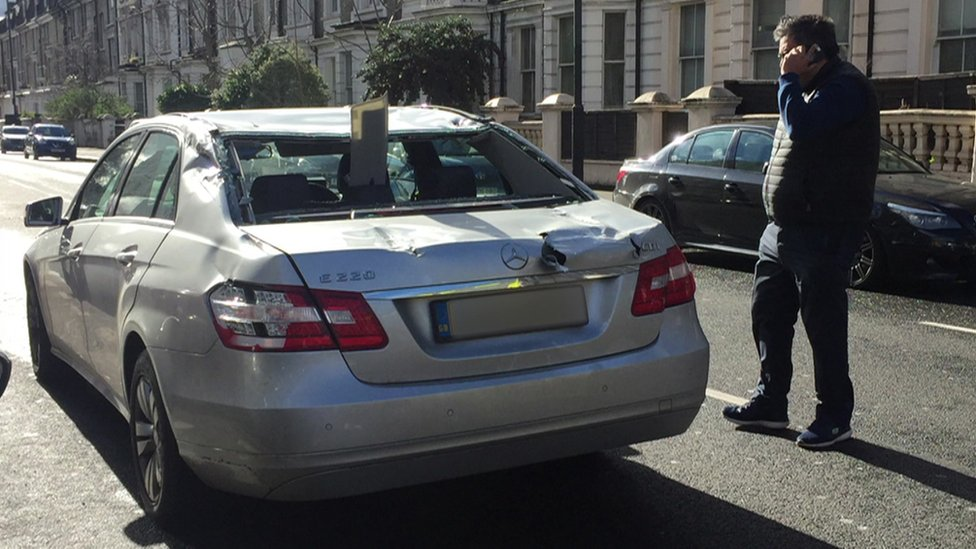 Car with plank of wood through back window