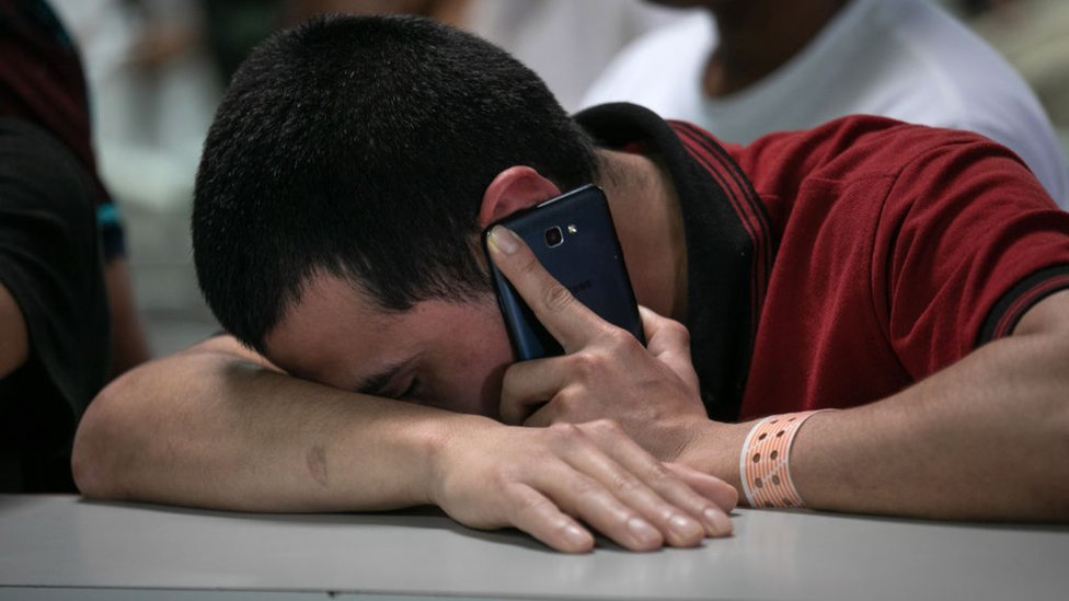 Un joven inmigrante sosteniendo un teléfono celular