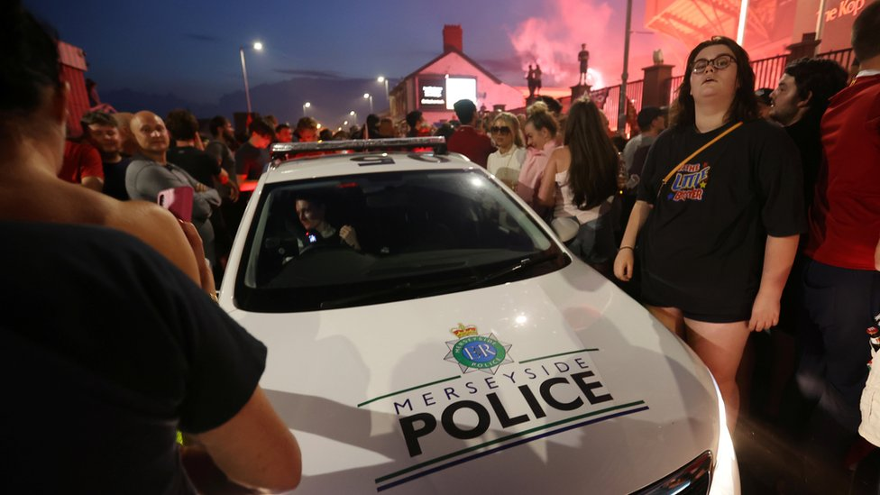 Police car cuts through crowd outside Anfield