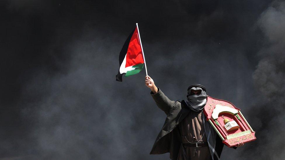 Un manifestante palestino ondea una bandera en medio del humo