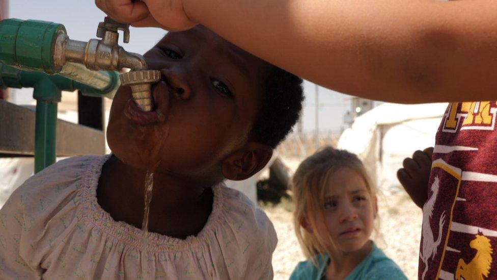طفل يشرب الماء من الصنبور
