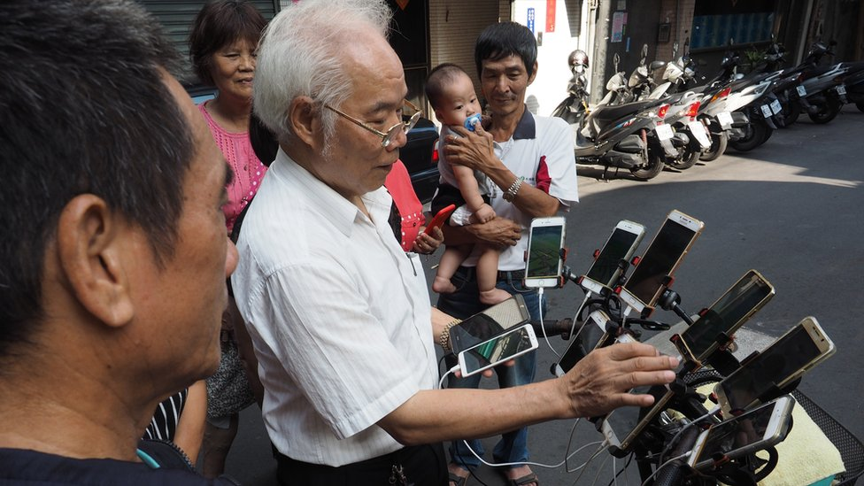 Chen San-yuan shows his Pokemon Go set up to passersby