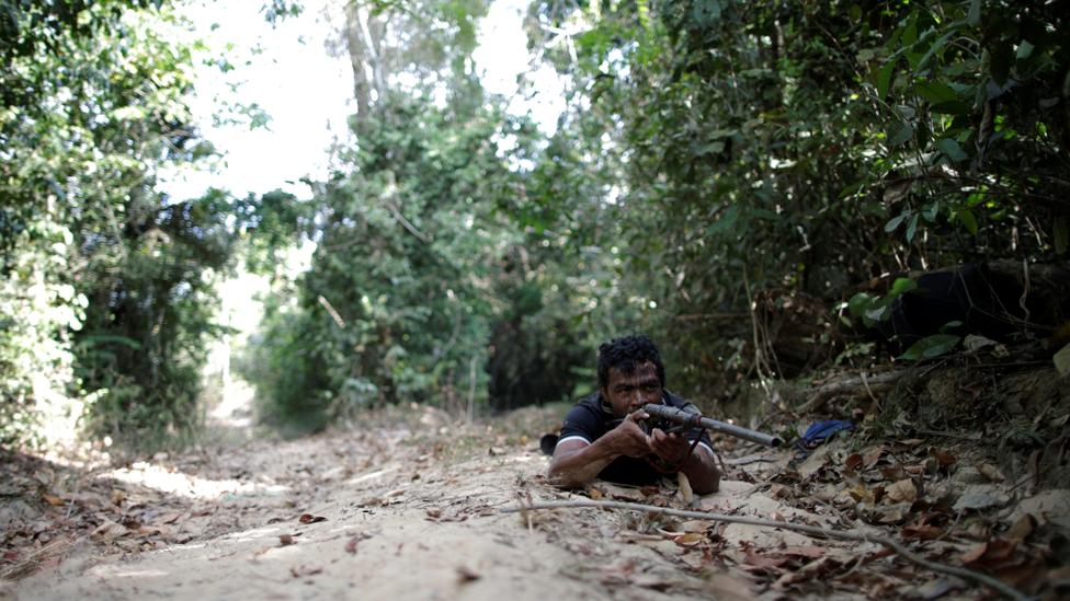 Paulo Paulino Guajajara en el suelo con un rifle