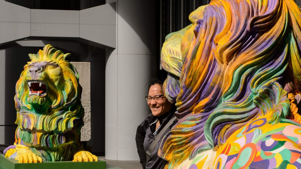 """A woman poses between a pair of lions painted in rainbow stripes displayed outside HSBC""""s main office in Hong Kong on December 6, 2016"""