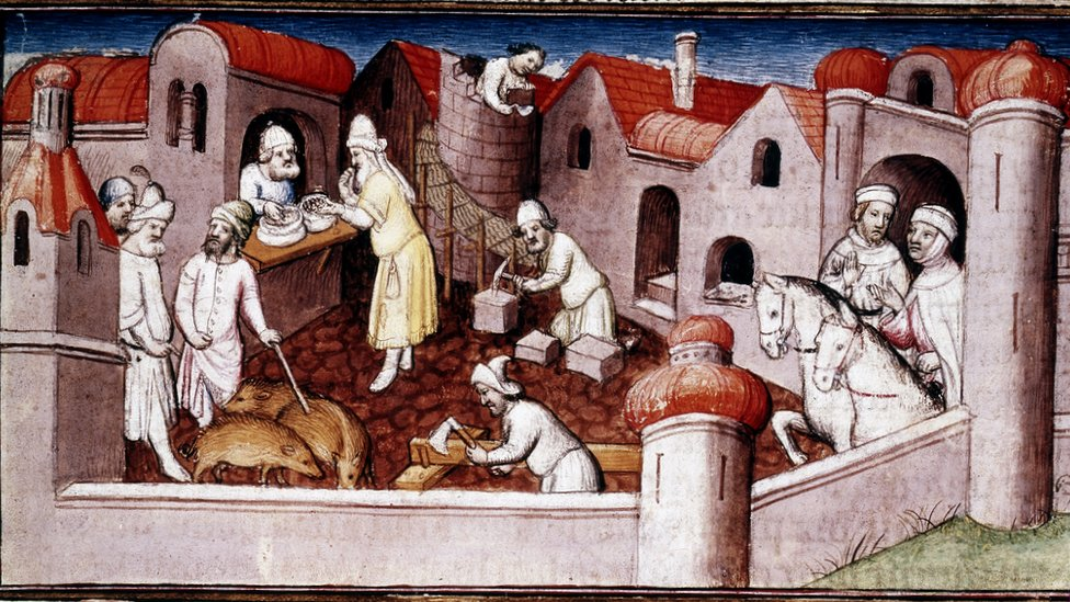 Scene from Marco Polo's Book of Marvels, early 15th century, showing merchants entering a walled town, mason and carpenter at work, a shopkeeper serving a customer, and men driving swine
