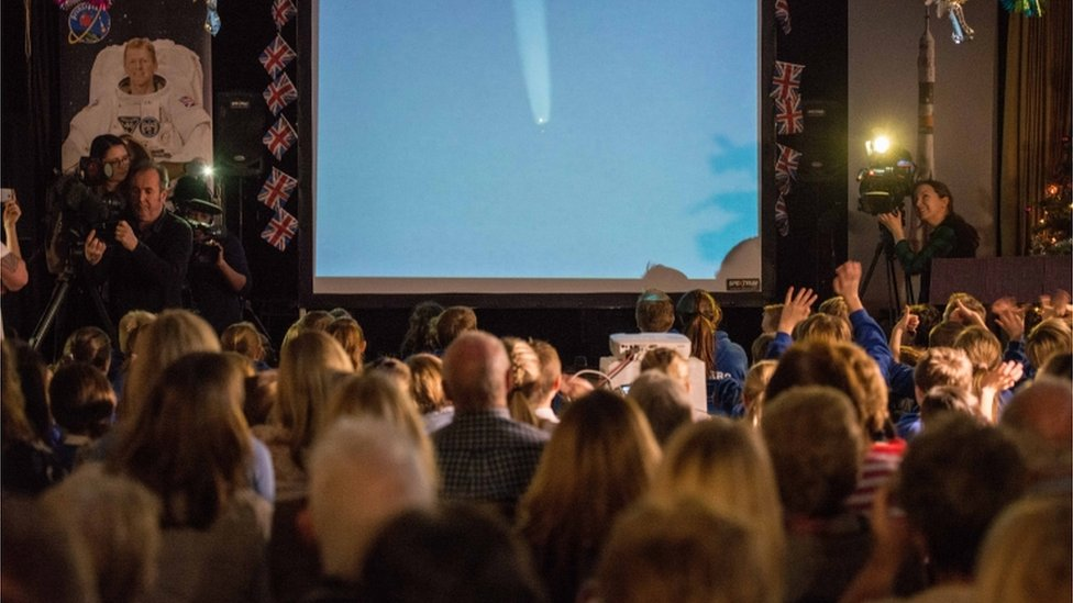 People gathered in a hall watching a space launch on a big screen
