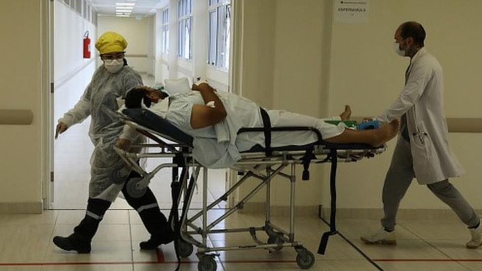 Profissionais de saúde carregam paciente em maca
