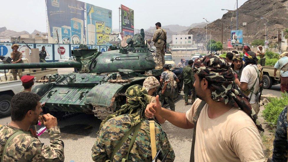 يمنيون مناصرون لحركة انفصالية جنوبية إلى جوار دبابة استحوذوا عليها من قاعدة عسكرية قريبة في مدينة عدن الجنوبية في 10 أغسطس/آب 2019