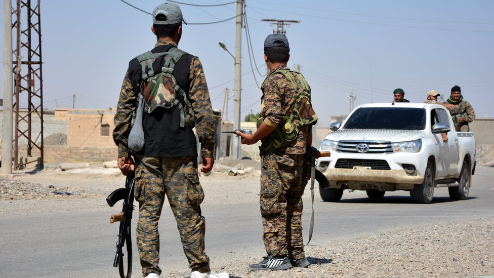 Syrian Democratic Forces fighters stand guard on the outskirts of Raqqa, Syria (11 June 2017)